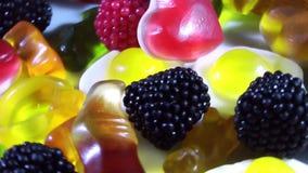 Zuccheri la caramella gommosa della gelatina di colore che gira sulla tavola stock footage