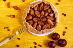 Zuccheri la torta libera con le prugne e l'uva passa su un piatto bianco su fondo di legno giallo decorato con tre prugne fresche Fotografia Stock Libera da Diritti