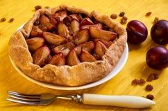 Zuccheri la torta libera con le prugne e l'uva passa su un piatto bianco su fondo di legno giallo decorato con tre prugne fresche Immagine Stock
