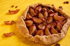 Zuccheri la torta libera con le prugne e l'uva passa sulla fine di legno gialla del fondo su decorate con l'uva passa marrone ed  Fotografia Stock Libera da Diritti