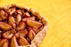 Zuccheri la torta libera con le prugne e l'uva passa sulla fine di legno gialla del fondo su con lo spazio della copia dalla dest Fotografia Stock