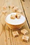 Zuccheri marrone e bianco in una ciotola di legno su un bordo Immagini Stock Libere da Diritti