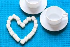 Zucchero bianco nella forma del cuore sul tovagliolo blu Immagine Stock