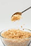 Zucchero di canna che cade da un cucchiaino da tè Fotografia Stock