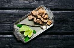 Zucchero di canna con le foglie di menta e della calce in un vassoio sul vecchio di legno Fotografia Stock