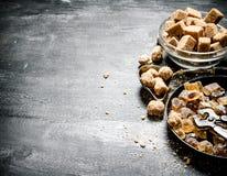 Zucchero di canna di Brown Su fondo rustico nero Immagine Stock