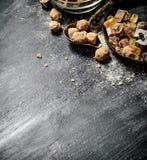 Zucchero di canna di Brown Su fondo rustico nero Immagini Stock Libere da Diritti