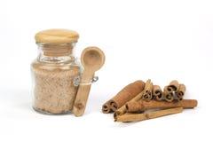 Zucchero di Cinamon con i bastoni del cinamon isolati su bianco Fotografia Stock