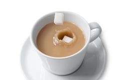 Zucchero di cubo che cade nella tazza di tè Fotografia Stock