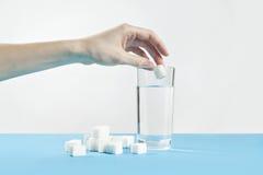 Zucchero di cubo e del bicchiere d'acqua, malattia del diabete, dipendenza dolce, goccia della mano uno zucchero Fotografie Stock Libere da Diritti