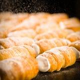 Zucchero di polvere che cade sopra per scremare i corni Fotografia Stock