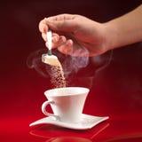Zucchero di versamento della mano in tazza di caffè Immagini Stock