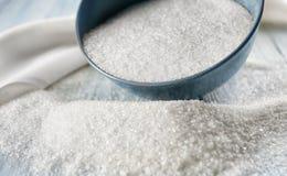 Zucchero granulato di bianco sparso dalla ciotola fotografie stock