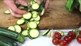 Zucchini affettati con la ciliegia e lo zucchini fresco delle erbe con basilico sulla tavola di legno archivi video