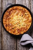 Zucchini, bacon and cheese casserole or gratin. In cast-iron pan on vintage wooden table. Selective focus royalty free stock images