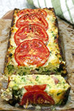 Zucchini and Bacon Slice. Topped with tomatoes,  straight out of the baking tin Royalty Free Stock Photography