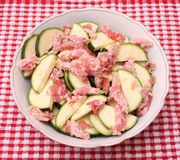 Zucchini and bacon. Some raw zucchini and bacon in a white bowl Royalty Free Stock Photography
