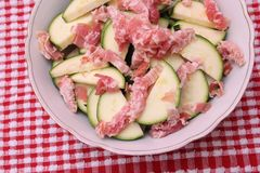 Zucchini and bacon. Some raw zucchini and bacon in a white bowl Stock Photos