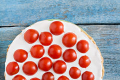 Zucchini cake with tomatoes on a blue wooden background.  royalty free stock image