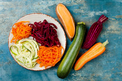 Zucchini, carrot, sweet potato and beetroot noodles on a plate. Top view, overhead. Blue rustic background. Zucchini, carrot, sweet potato and beetroot noodles royalty free stock photography