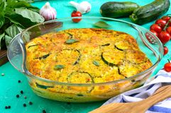 Zucchini, cheese, eggs, cream and green casserole in a transparent glass form on a bright background. Tasty healthy dish.  stock image