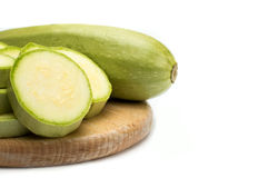 Zucchini. On circle wooden plate on white isolated background royalty free stock photography