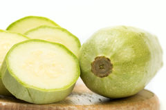 Zucchini. On circle wooden plate on white isolated background royalty free stock photo