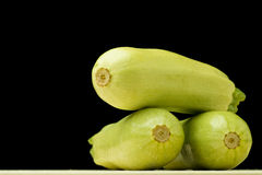 Zucchini. On circle wooden plate on white isolated background stock images