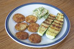 Zucchini Cooked Three Ways. A plate of zucchinni cooked three different ways, fried, grilled and a spaghetti zucchini with garlic sauce stock photos