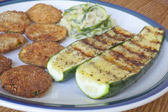 Zucchini Cooked Three Ways. A plate of zucchinni cooked three different ways, fried, grilled and a spaghetti zucchini with garlic sauce Royalty Free Stock Images