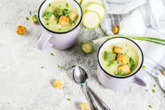 Zucchini creamy soup. Two portions of homemade zucchini creamy soup with bread crumbs in mugs on a light concrete background. top view royalty free stock image