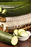 Zucchini (Cucurbita pepo). Closeup of a sliced zucchini  over a wooden table Royalty Free Stock Images