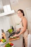 Zucchini da estaca da mulher nova na cozinha Foto de Stock