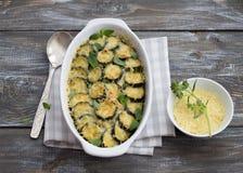 Zucchini del gratin con formaggio e verdi su un fondo di legno Fotografia Stock Libera da Diritti