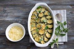 Zucchini del gratin con formaggio e verdi su un fondo di legno Fotografia Stock