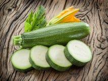 Zucchini e fetta dello zucchini con il fiore e la foglia su backg di legno Immagine Stock