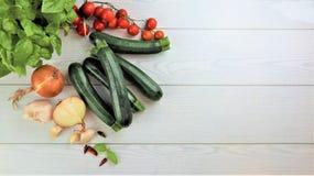 Zucchini f?r ny gr?nsak, tomater, basilika mot arkivbild