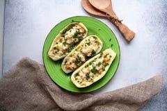 Zucchini farcito con il tacchino, il pomodoro, il formaggio e la cipolla di inverno su un piatto verde immagine stock libera da diritti