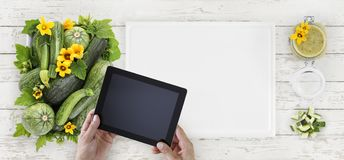 zucchini, flowers and green sauce food top view, hands with digital tablet on white cutting board in kitchen wooden worktop stock image