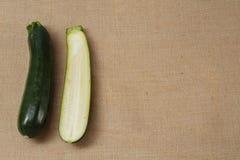 Zucchini fresco che si trova su una superficie della tela di sacco immagini stock