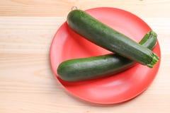 Zucchini fresco su un piatto rosso e su un fondo di legno Alimento sano immagini stock
