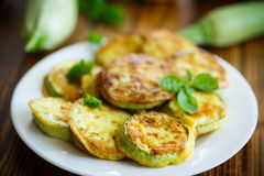 Zucchini fried in batter. On a wooden table Royalty Free Stock Photos