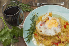 Zucchini with fried egg. Zucchini stew, zucchini with fried egg, glass of wine, vine leaves Royalty Free Stock Images