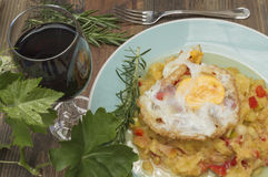 Zucchini with fried egg. Zucchini stew, zucchini with fried egg, glass of wine, vine leaves Stock Photos