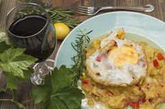 Zucchini with fried egg. Zucchini stew, zucchini with fried egg, glass of wine, vine leaves Royalty Free Stock Photography
