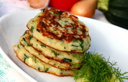 Zucchini fritters. Pile of zucchini fritters on plate with cucumber and dill royalty free stock image