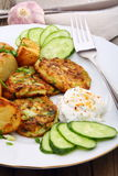 Zucchini Fritters and slices of new potatoes. Royalty Free Stock Photos