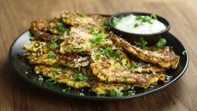 Zucchini fritters, vegetarian zucchini pancakes, served with fresh herbs and garlic yogurt sauce royalty free stock photography