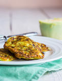 Zucchini fritters on a white plate, green cloth Stock Image