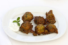 Zucchini fritters with yogurt dressing. On white plate royalty free stock photo
